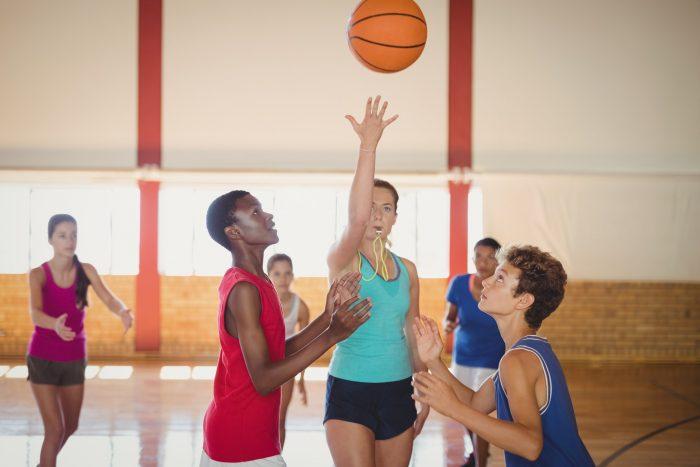Naiset pelaavat koripalloa sääntöjen mukaan
